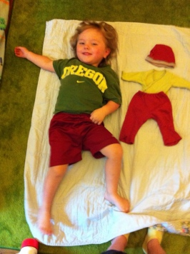 Three Year Old Boy Next to Preemie Outfit